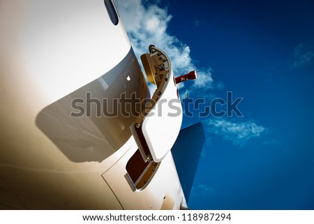 open door and tail in private jet against the blue sky - stock photo