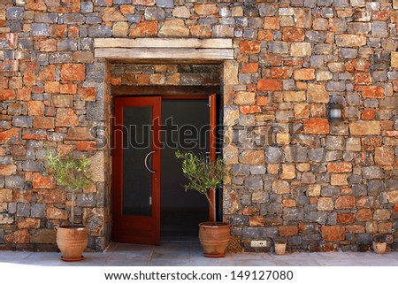 Open door and terracotta pots with young olive tree against a stone mediterranean wall(Greece) - stock photo