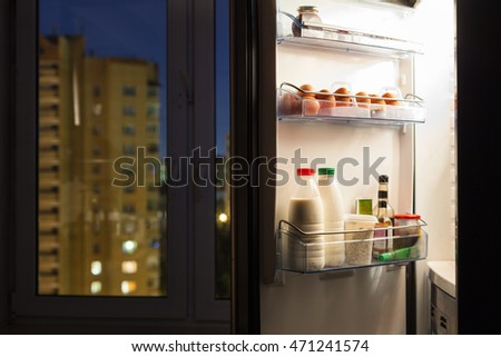 Open door of home fridge with dairy products and view of city through window in night