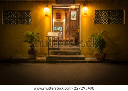Open door to old cafe in Hoi An. Restaurant at night in Vietnam, Asia. Stand with menu at entrance. Plants in pots. Light from lamps. Traditional asian place to eat. Beautiful design of windows. - stock photo