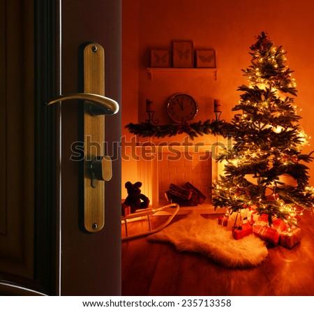 Open door with decorated Christmas tree in room - stock photo