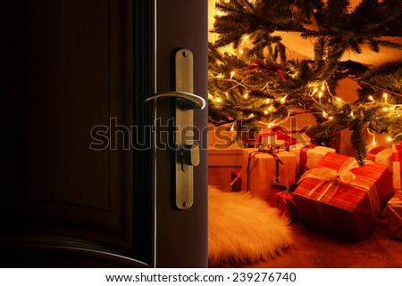 Open door with decorated Christmas tree in room - stock photo