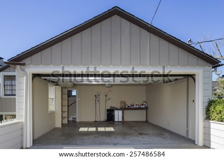 Open double Garage in grey and blue sky with peak roof. - stock photo
