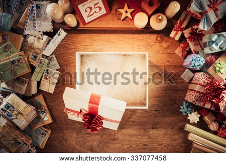 Open empty Christmas gift box on a wooden desktop surrounded by letters and presents, top view - stock photo