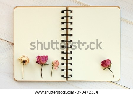 Open empty copy book with dried roses. Blank creamy pages. - stock photo