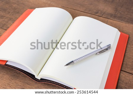 Open empty notebook with pen. - stock photo