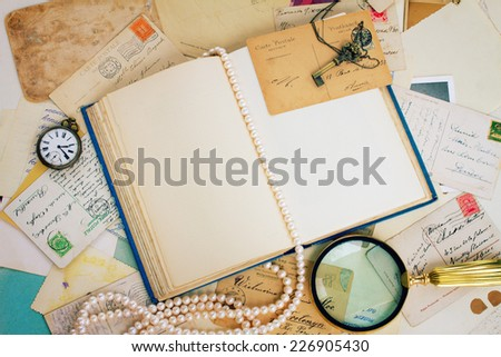 open empty old book with  finding glass, antique postcards and strand of pearls vintage background with copy space - stock photo