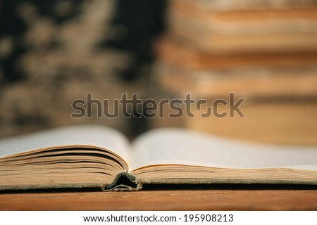 open end of the old book on a wooden boards background on a pile of books