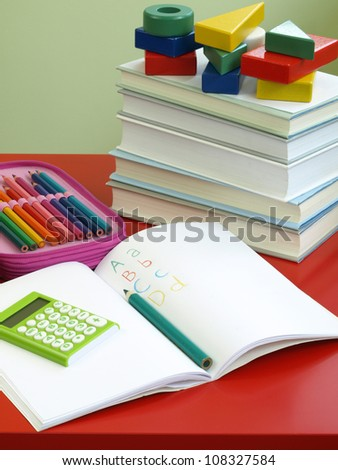 Open exercise book with calculator and crayons - stock photo