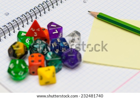 open exercise book with sticky card, pencil and role playing dices - stock photo - stock photo
