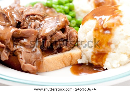 open faced diner style hot beef sandwich with mashed potatoes, gravy and fresh vegetables - stock photo