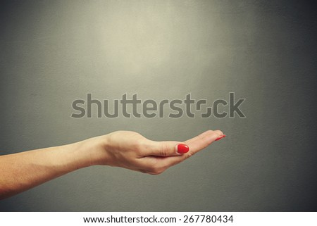 open female palm holding empty copyspace against dark background