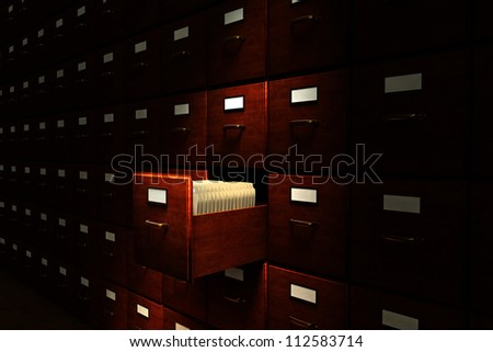 Open file drawer in a dark room filled with file cabinets - stock photo