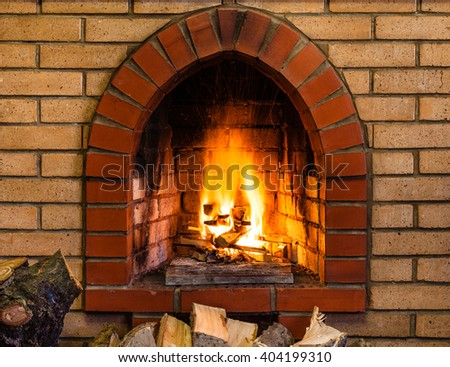open fire in indoor brick fireplace in country cottage - stock photo