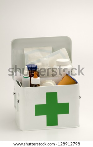 Open first aid kit filled with medical supplies in white background - stock photo