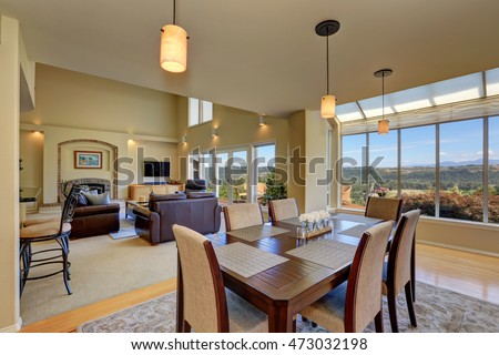Open floor dining room with wooden table set and pendant lights. Family room view. Northwest, USA