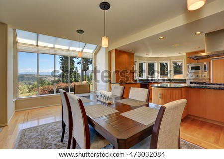 Open floor dining room with wooden table set and pendant lights. Kitchen room view. Northwest, USA