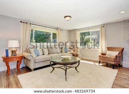 Open floor plan living room interior in white tones with hardwood floor. Also rug and nice coffee table. Northwest, USA