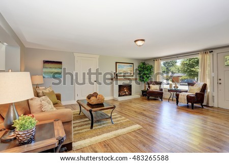 Open floor plan living room interior in white tones with hardwood floor. Also white brick fireplace. Northwest, USA