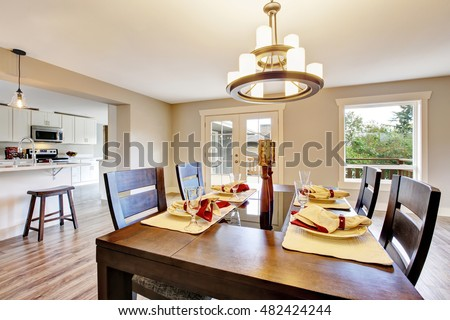 Open floor plan spacious room interior. Dining area with dark brown wooden table set. Northwest, USA