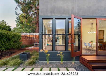 Open french doors leading into contemporary home with wooden terrace in Zen Garden style, open floor plan and greenery at night. Large window showing modern interior at twilight.  - stock photo