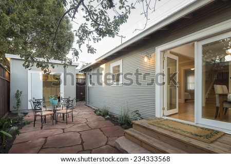 Open french doors leading to outdoor area of traditional California home with seating arrangement and shed / bungalow with matching design and colors.  - stock photo