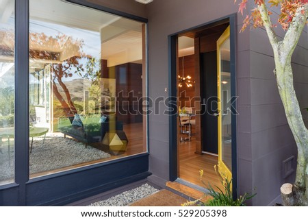 Open Front Door With Large Window Next To It.