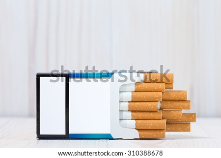 Open full pack of cigarettes on white wood background - stock photo