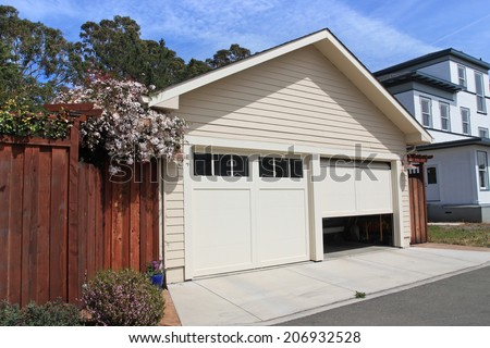 Open garage door in suburban house  - stock photo