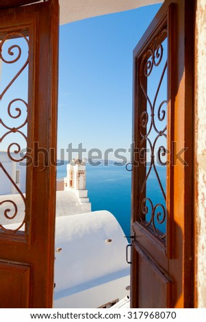 Open gate leading to a summer resort with a sea view in Oia, Santorini - stock photo