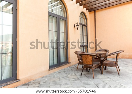 Open gazebo with rattan chairs and table in a patio - stock photo