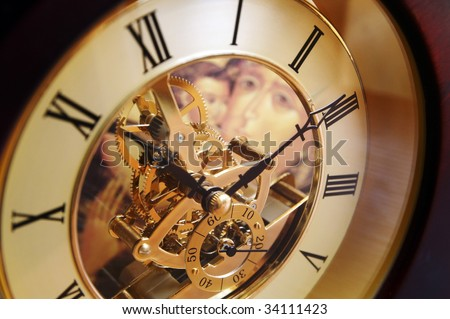 Open-gearing transparent clock with the Virgin Mary icon appearing through glass, blur background - stock photo
