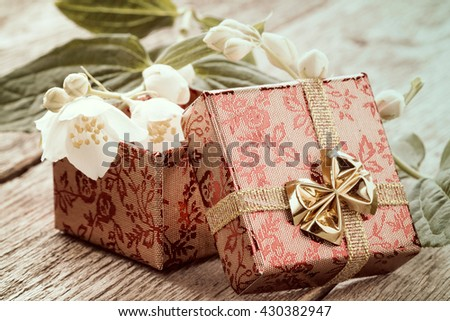 Open gift box and wild flower on a wooden background