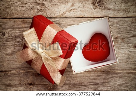 Open gift box with a cute little heart inside. On old wood background. - stock photo