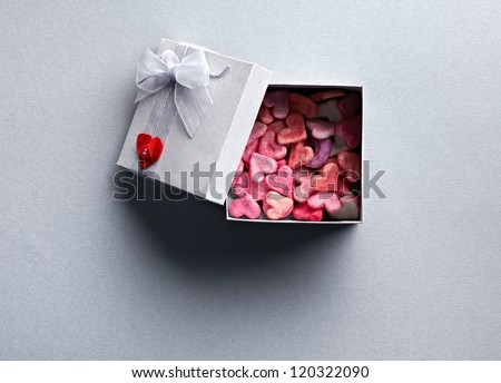 Open gift box with lots of cute little hearts inside. On gray textured paper background. - stock photo