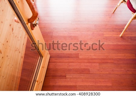 Open Glass door leading onto luxury wooden porch shot from above showing a richness of wood colors and wooden grain textures