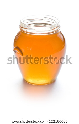Open glass jar full of honey isolated on white background