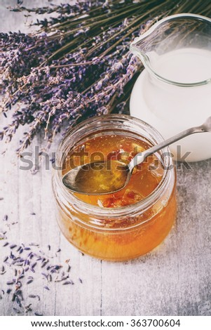 Open glass jar of liquid honey with honeycomb and silver spoon inside, glass jug of milk and bunch of dry lavender over white wooden surface Rustic style. With retro filter effect - stock photo