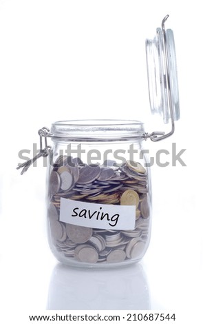 Open glass jar with coin and 'saving' text - stock photo