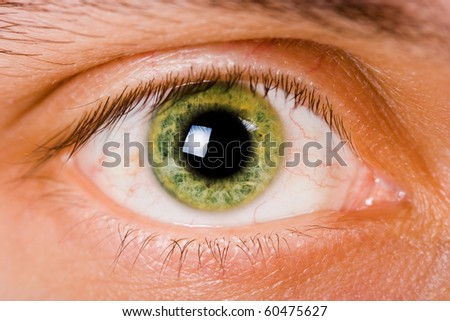 open green eye men. Close-up with bright light - stock photo