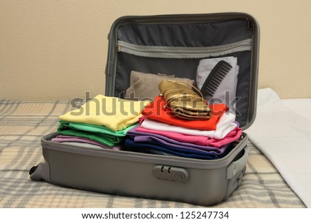 Open grey suitcase with clothing on bed - stock photo