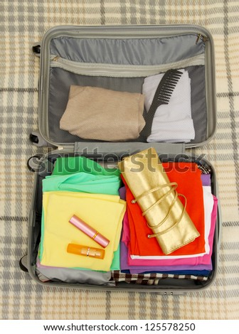 Open grey suitcase with clothing on plaid - stock photo