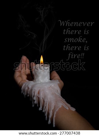 Open hand holding a candle stick with wax flowing down the arm