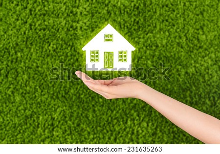 Open hand holding a house isolated on green background.
