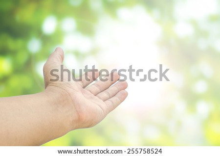 open hand on blurred abstract nature background