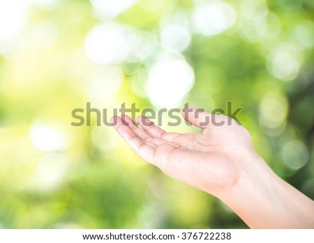 Open hand with blur nature green bokeh background