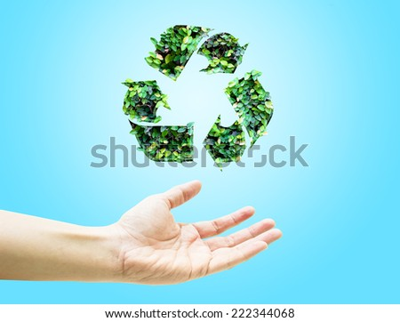 Open hand with green leaf recycle icon on light blue background - stock photo