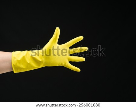 open hand with yellow rubber glove on black background - stock photo