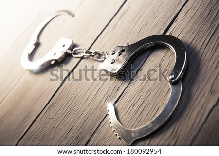 Open handcuffs, liberty concept on a wooden background - stock photo