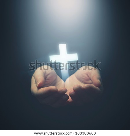 Open hands holding cross, symbol of Christian faith - stock photo